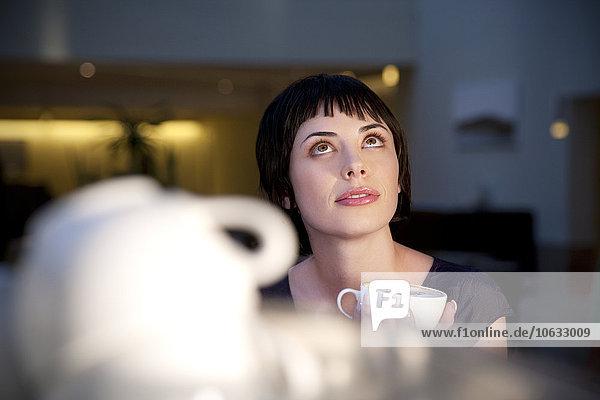 Junge Frau hält eine Tasse Kaffee und schaut nach oben. Junge Frau hält eine Tasse Kaffee und schaut nach oben.