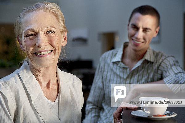 Porträt der lächelnden Seniorin mit Tasse Kaffee und jungem Mann im Hintergrund
