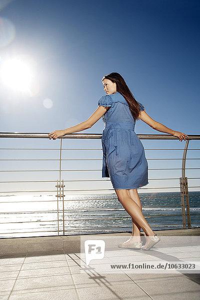 Junge Frau  die sich auf das Geländer am Meer stützt