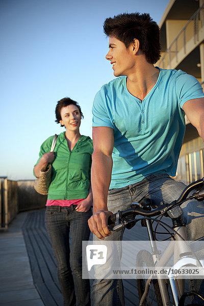 Junger Mann mit Fahrrad und Frau  die ihm folgt Junger Mann mit Fahrrad und Frau, die ihm folgt
