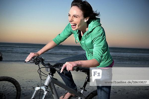 Unbeschwerte junge Frau auf dem Mountainbike am Strand Unbeschwerte junge Frau auf dem Mountainbike am Strand