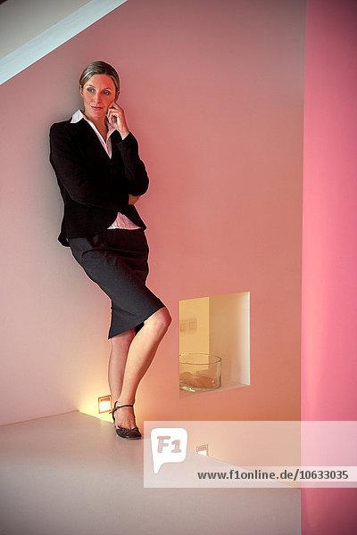 Porträt einer nachdenklichen Geschäftsfrau  die sich an eine Wand lehnt. Porträt einer nachdenklichen Geschäftsfrau, die sich an eine Wand lehnt.