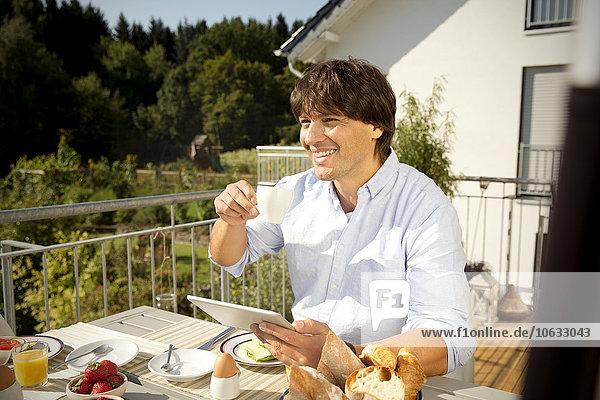 Smiling man with digital tablet having breakfast on balcony