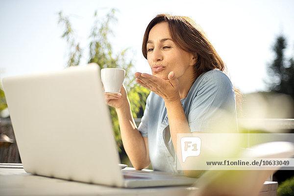 Frau auf dem Balkon mit Videokonferenz auf dem Laptop