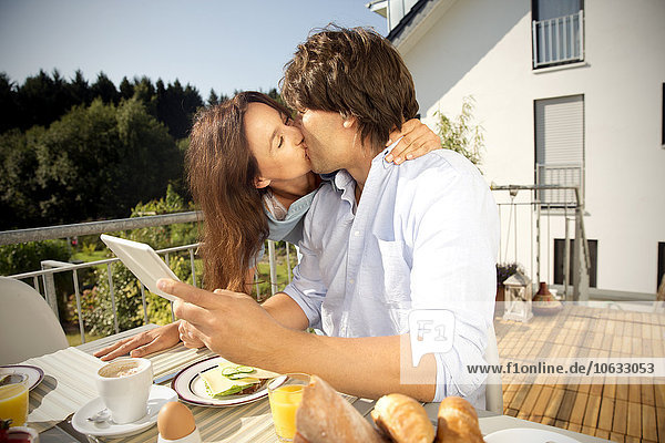 Frau küsst Mann auf Balkon am Frühstückstisch