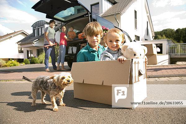 Zwei Brüder mit Hund im Karton unterwegs mit Familie im Hintergrund