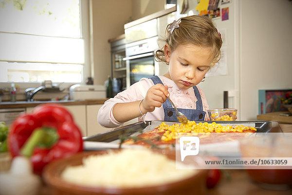 Mädchen in der Küche bereitet Pizza zu