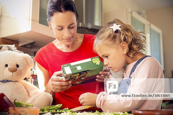 Mutter und Tochter in der Küche bei der Zubereitung der Pizza