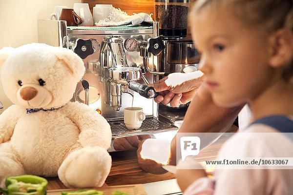 Mädchen mit Teddybär in der Küche mit Vater mit Kaffeemaschine