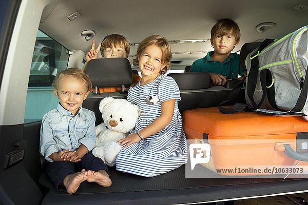 Glückliche Kinder im Kofferraum mit Teddy