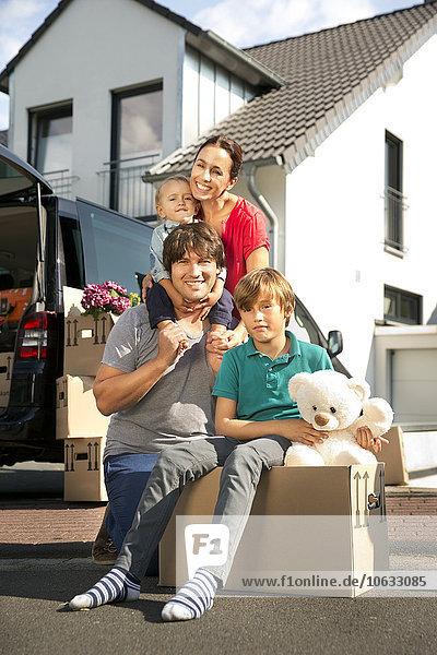 Glückliche Familie mit zwei Söhnen beim Umzug