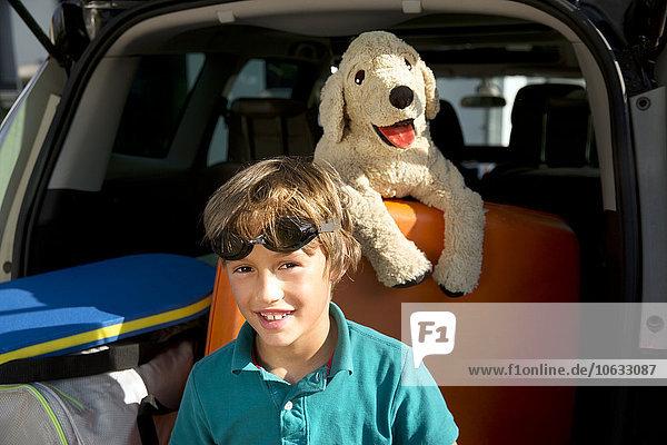 Lächelnder Junge im Kofferraum mit Schwimmbrille und Kuscheltier