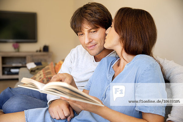 Couple reading a book on couch