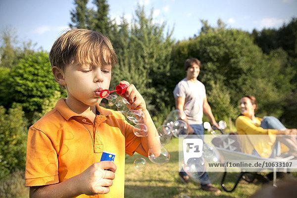 Glückliche Familie im Garten mit Mann  der Frau in Schubkarre schiebt und Junge  der Seifenblasen bläst.