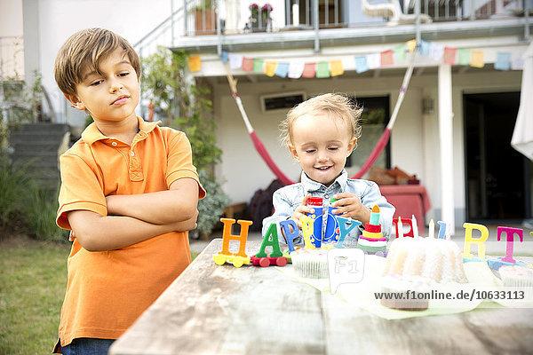 Fröhliches Kleinkind feiert Geburtstag im Garten mit unzufriedenem Bruder  der daneben steht.