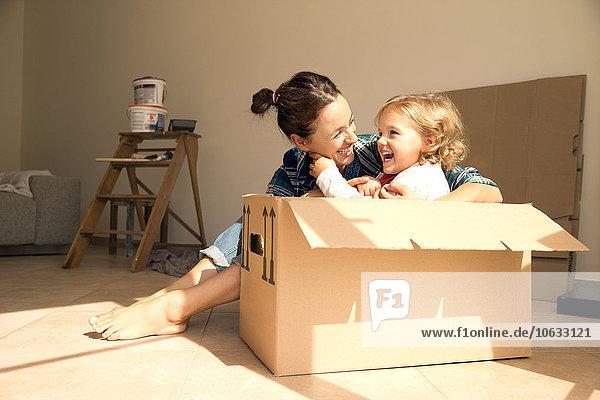 Lachende Frau mit Tochter im Karton sitzend