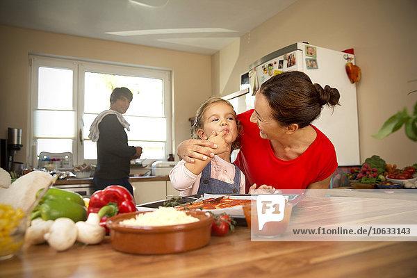 Glückliche Mutter und Tochter in der Küche bereiten Pizza mit Vater im Hintergrund zu