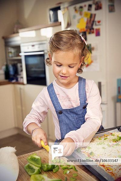 Girl in kitchen preparing pizza