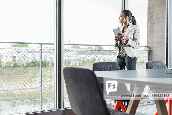 Junge Frau mit digitalem Tablett im Büro mit Blick aus dem Fenster