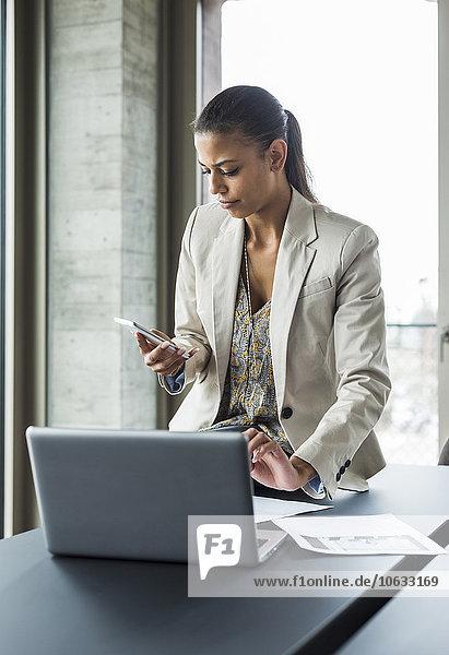 Junge Frau im Büro mit Laptop und Handy