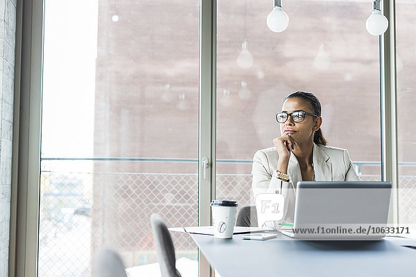 Junge Frau im Konferenzraum mit Laptop
