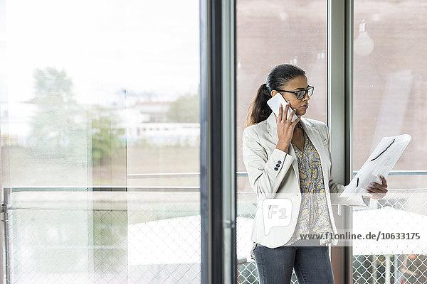 Junge Frau im Büro am Handy
