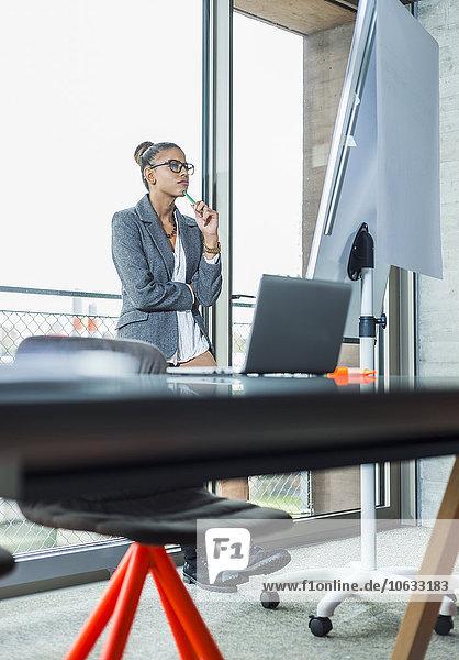 Junge Frau im Büro mit Blick auf Flipchart