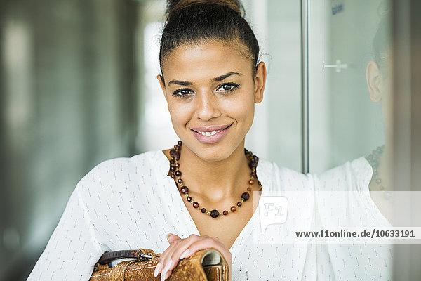 Porträt einer lächelnden jungen Frau  die sich an die Glaswand lehnt.