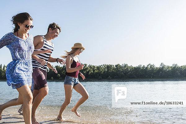 Glückliche Freunde beim Laufen am Fluss