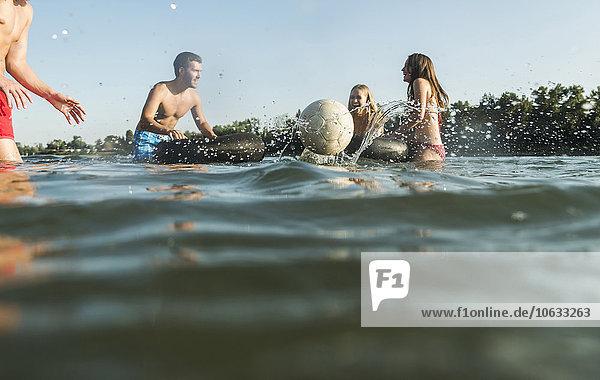 Glückliche Freunde mit Schläuchen und Ball im Wasser