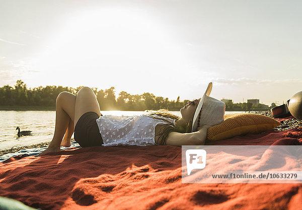 Junge Frau entspannt sich bei Sonnenuntergang am Flussufer