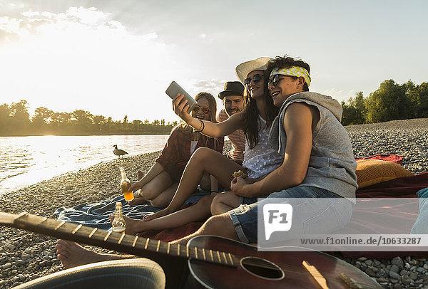 Freunde  die bei Sonnenuntergang einen Selfie am Flussufer nehmen.