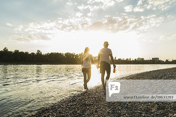 Paar  das bei Sonnenuntergang Hand in Hand am Flussufer spazieren geht.