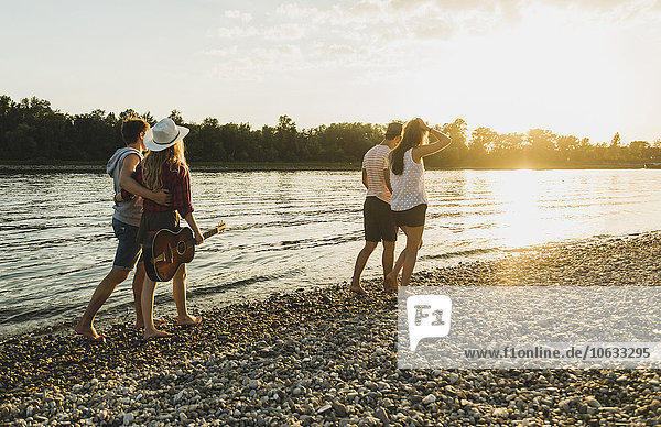 Two couples walking at the riverside at sunset