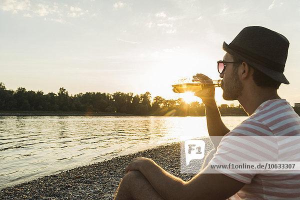 Junger Mann beim Biertrinken am Flussufer bei Sonnenuntergang