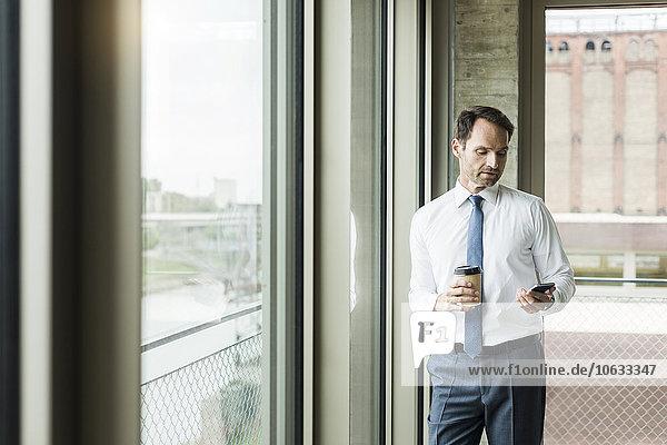 Porträt eines Geschäftsmannes mit Kaffee zum Anschauen seines Smartphones