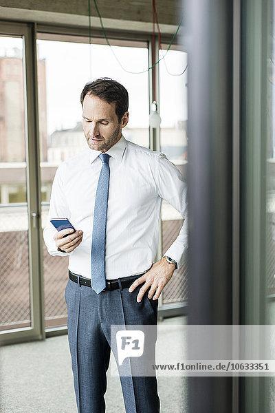 Porträt eines Geschäftsmannes mit Blick auf sein Smartphone