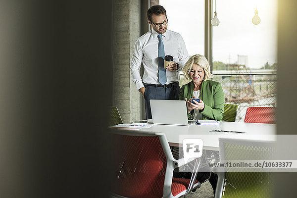Zwei Geschäftsleute  die ein Smartphone in einem Büro betrachten