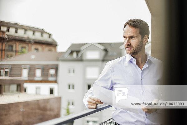 Porträt eines Geschäftsmannes mit einem Blatt Papier und einem Smartphone in der Ferne