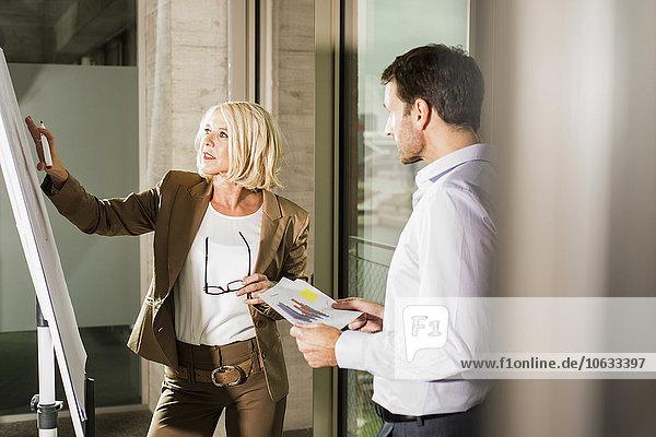 Geschäftsfrau erklärt ihrem Geschäftspartner eine Grafik