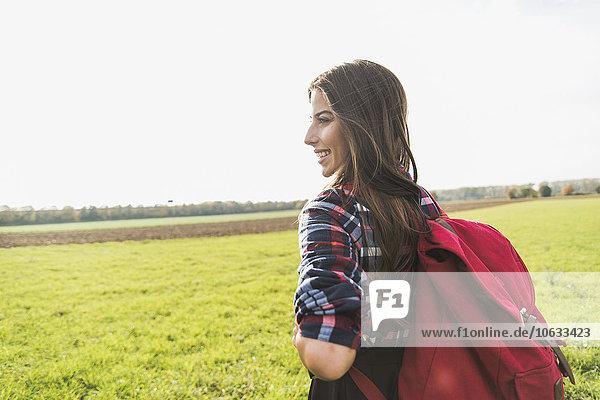 Lächelnde junge Frau mit Rucksack auf dem Land