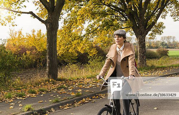 Junge Frau beim Radfahren in der Herbstlandschaft