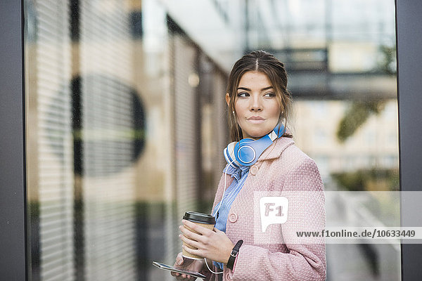 Young woman holding cell phone and coffee to go
