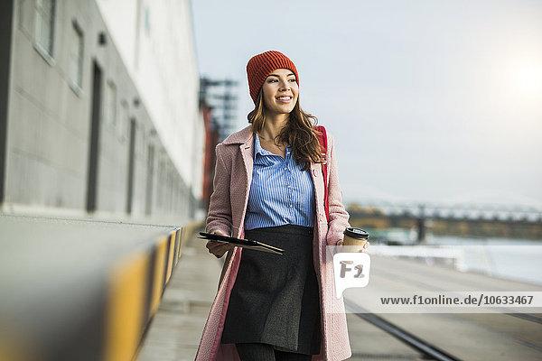 Lächelnde junge Frau am Flussufer mit Dokumenten und Kaffee zum Mitnehmen