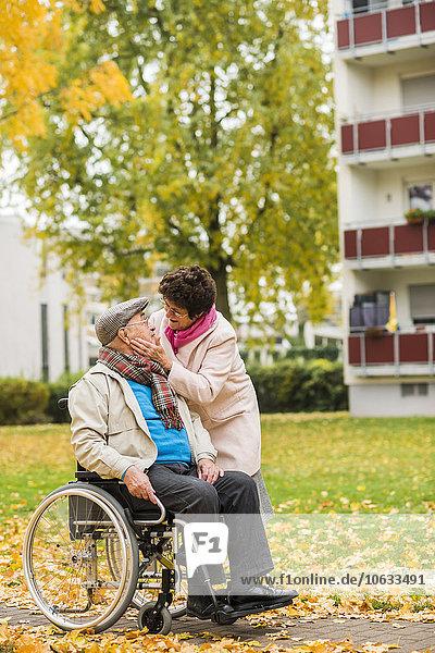 Seniorenfrau sieht Mann im Rollstuhl an