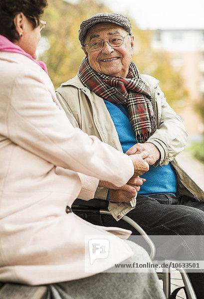 Älterer Mann im Rollstuhl hält Hände mit Frau auf der Bank