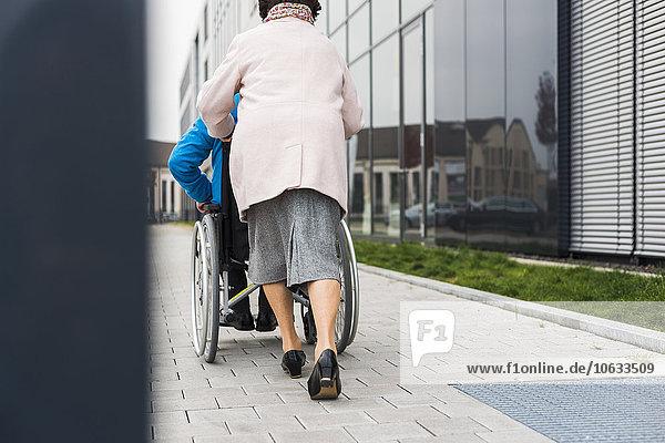 Seniorin schiebt Ehemann im Rollstuhl auf dem Bürgersteig