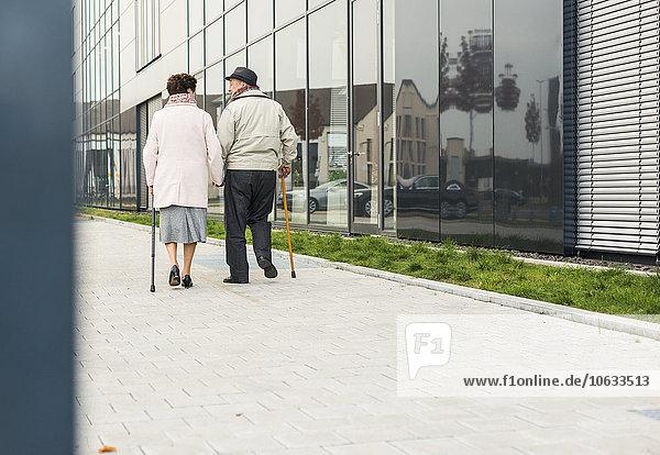Seniorenpaar mit Gehstöcken auf dem Gehsteig