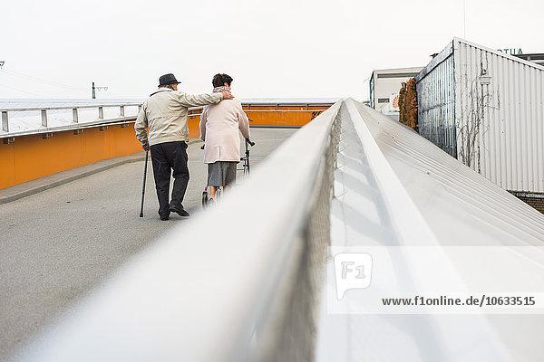 Senior couple walking with walking stick and wheeled walker