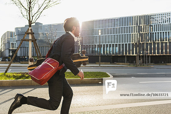 Germany  Frankfurt  Young businessman running with skateboard under his arm  using mobile phone